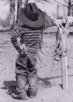 Young boy dressed in western wear with a lasso, symbolizing a green hat hacker.