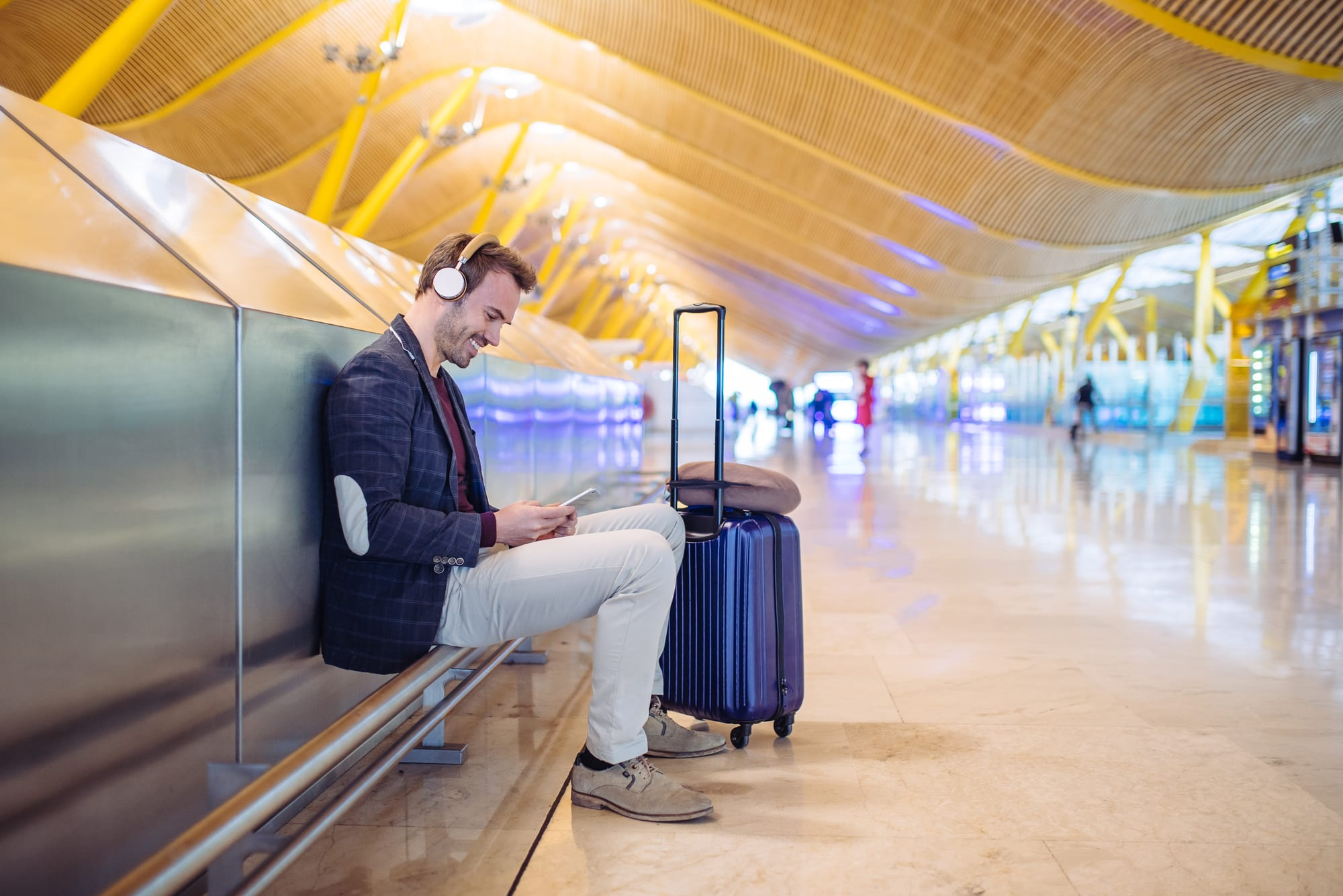 Traveler with electronic device, noice cancelling headphones and neck pillow. The best tech gadgets for travelers improve time spent away from home.