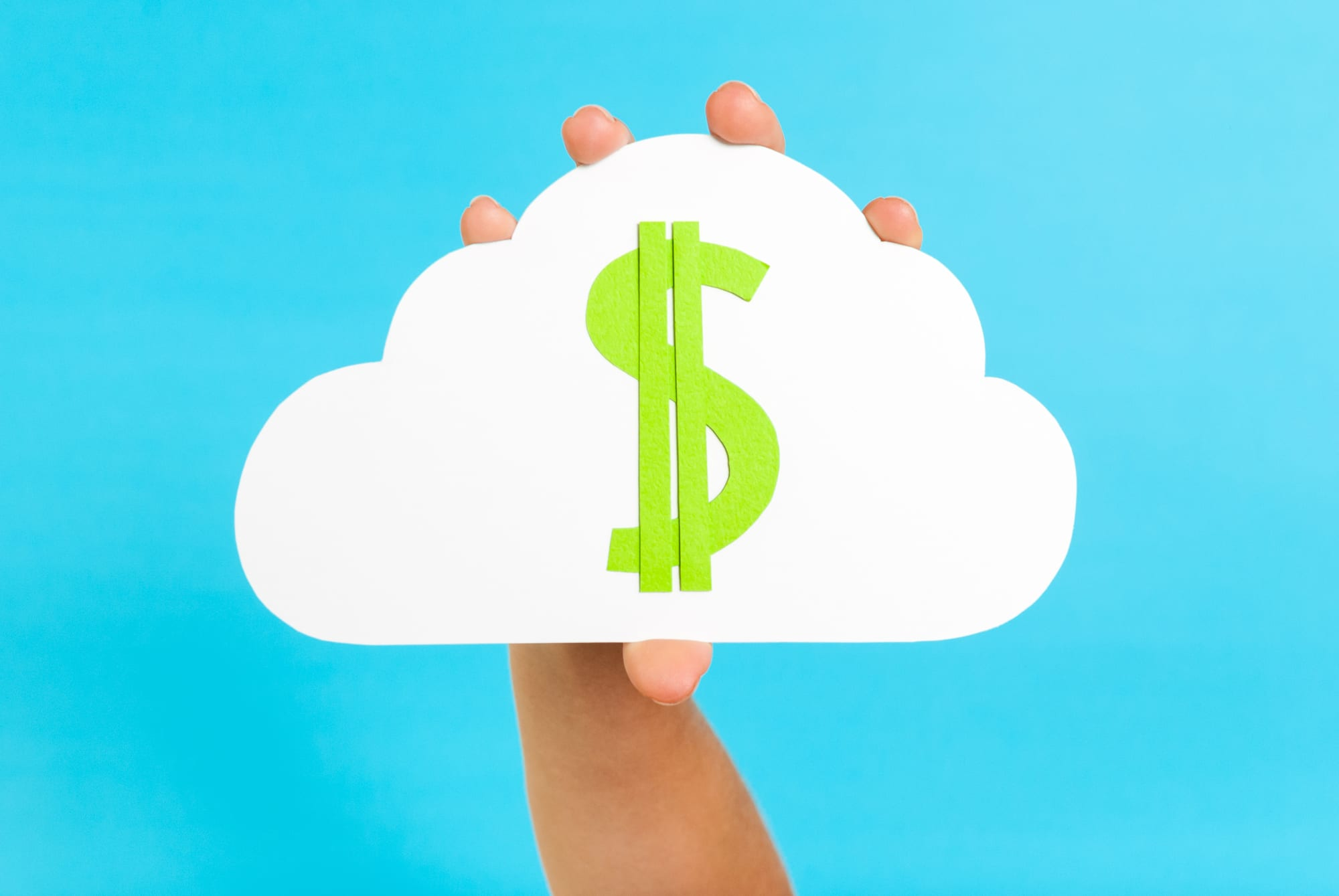 Hand holding a cloud with a dollar sign symbolizing costs related to cloud computing.
